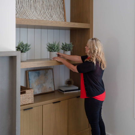 woman straightening plant on bookcase